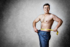 Man with measuring tape. Image of a man in blue jeans with measuring tape who has lost body weight Royalty Free Stock Image