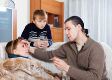 Man measuring the temperature of ill wife. At home royalty free stock photography