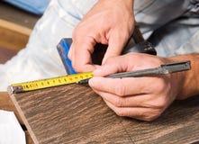 Man measuring a tile piece with a marker Stock Photos