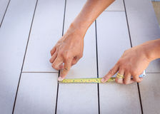 Man measuring timber floor with measuring tape. Royalty Free Stock Photo