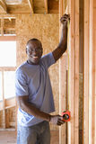 Man measuring wall in partially built house, smiling, portrait Royalty Free Stock Photo