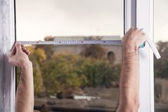 Man measuring window. Installing new window in house royalty free stock image