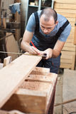 Man measuring a wood plank Stock Photo