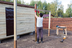 Man measuring wooden post on the level Stock Image