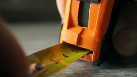 Man measuring with yellow tape measure macro video stock video