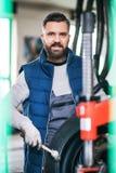 Man mechanic repairing a car in a garage. Mature man mechanic repairing a car in a garage Royalty Free Stock Photo