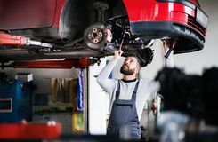 Man mechanic repairing a car in a garage. Mature man mechanic repairing a car in a garage Royalty Free Stock Photos