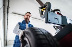 Man mechanic repairing a car in a garage. Mature man mechanic repairing a car in a garage Stock Photo
