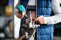 Man mechanic repairing a car in a garage. Unrecognizable man mechanic repairing a car in a garage Stock Photo