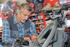 Man mechanic working on adjustments motorcycle Royalty Free Stock Photography