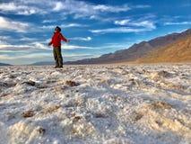 Man med öppna armar som står på den Badwater handfatet, Death Valley nationalpark Arkivbild