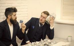 Man med allvarlig sinnesrörelse Den trötta mannen som håll skorrar mycket av kassa, kollega, rymmer kreditkorten Affärspartners a royaltyfria bilder