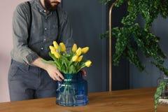 Man med att arbeta i trädgården passion som sätter gula tulpan och blå vasnolla royaltyfria foton