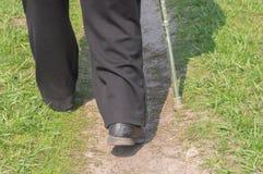 Man med att gå pinnen som bär gamla skrapade skor som går på en jordväg Arkivbilder
