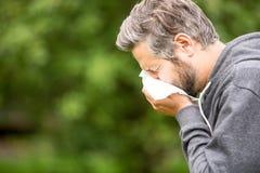 Man med att nysa för allergi royaltyfria bilder