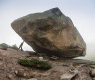 Man med att skjuta en enorm sten i Ergaki berg, Ryssland Arkivbild
