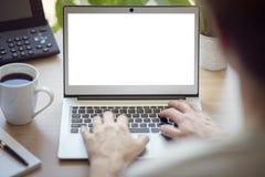 Man med bärbar datordatoren på kontorsskrivbordet med den tomma skärmen arkivfoton