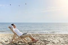 Man med bärbar datordatoren som kopplar av på stranden Arkivfoto
