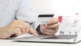 Man med bärbara datorn genom att använda kreditkorten white för shopping för backgraundinternetbärbar dator stock video