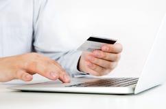Man med bärbara datorn genom att använda kreditkorten white för shopping för backgraundinternetbärbar dator Arkivbilder