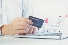 Man med bärbara datorn genom att använda kreditkorten white för shopping för backgraundinternetbärbar dator Fotografering för Bildbyråer