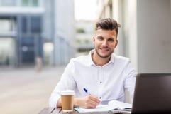 Man med bärbara datorn och kaffe på stadskafét royaltyfria bilder