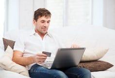 Man med bärbara datorn och kreditkorten hemma Arkivfoto