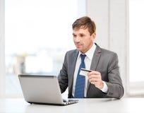 Man med bärbara datorn och kreditkorten i regeringsställning royaltyfri bild