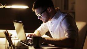 Man med bärbara datorn och legitimationshandlingar som arbetar på nattkontoret arkivfilmer
