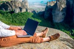 Man med bärbara datorn på bergen Arkivbild