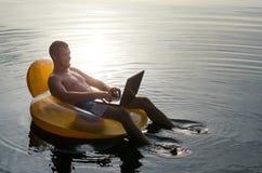 Man med bärbara datorn på en rubber cirkel i vattnet på solnedgången, fri sp Arkivfoton