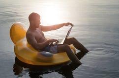Man med bärbara datorn på en rubber cirkel i vattnet på solnedgången, fri sp Royaltyfria Bilder
