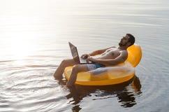 Man med bärbara datorn på en rubber cirkel i vattnet på solnedgången, fritt utrymme Royaltyfria Foton