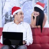 Man med bärbara datorn på soffan, medan se hans fru Arkivfoton