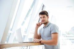 Man med bärbara datorn som dricker kaffe och inomhus ser kameran Royaltyfria Foton