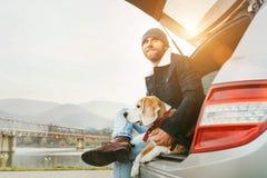 Man med beaglehunden som tillsammans placerar i bilstam Sen höstsi royaltyfria bilder