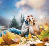 Man med beaglet på höstsiktslandskap arkivfoto