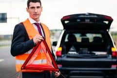 Man med bilsammanbrottet som reser upp varningstriangeln Arkivfoton