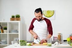 Man med blandaren och frukt som lagar mat hemmastatt kök arkivfoto
