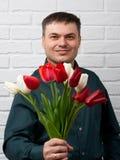 Man med blommor på det vita bakgrund för tegelstenvägg, ferie och hälsningsbegreppet Royaltyfria Foton