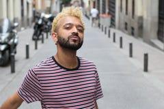 Man med blont färgat afro hår som utomhus poserar arkivfoton
