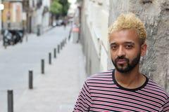 Man med blont färgat afro hår som utomhus poserar arkivbild