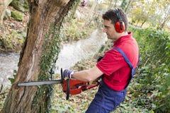 Man med chainsawen Arkivbild