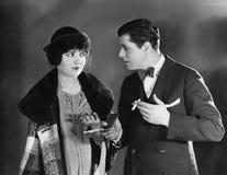 Man med cigaretter som talar till kvinnan (alla visade personer inte är längre uppehälle, och inget gods finns Leverantörgarantie Arkivfoto