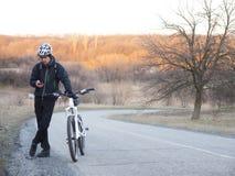 Man med cykelanseende på vägen och att se telefonen royaltyfri foto