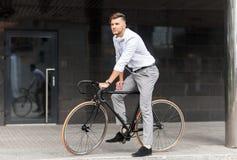 Man med cykeln och hörlurar på stadsgatan arkivfoton