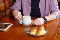 Man med den digitalt minnestavlan och drickakaffe Royaltyfri Foto
