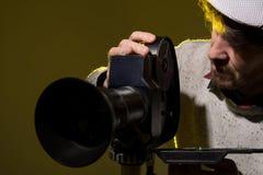 Man med den gamla filmfilmkameran. Skytte av filmen Arkivfoton