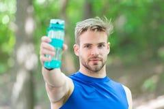 Man med den idrotts- utseendehållflaskan med vatten Manidrottsman nen i sport beklär utomhus- utbildning Sport och sunt Arkivfoto