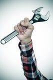 Man med den justerbara skiftnyckeln i hans hand, tillfogad karaktärsteckning Arkivfoto